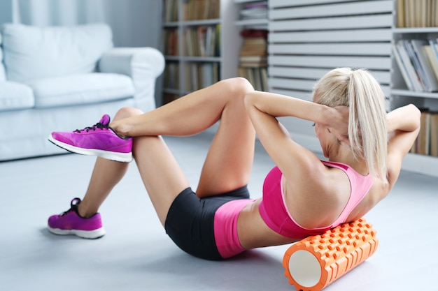 Blonde woman workout exercises with foam roller Free Photo