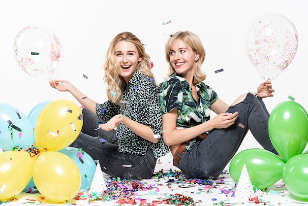 Blonde women  surrounded by confetti and balloons Free Photo