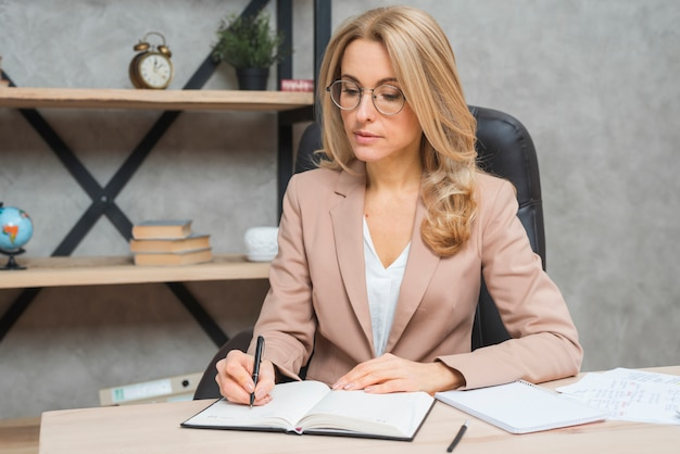 Blonde young businesswoman writing on diary with pen at office Free Photo