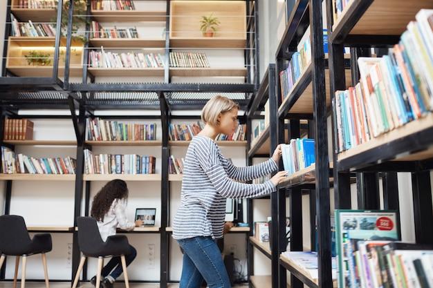 大学で試験の準備をしているストライプのシャツとジーンズで図書館の棚の本を探している金髪の若い見栄えの良い女性 無料写真