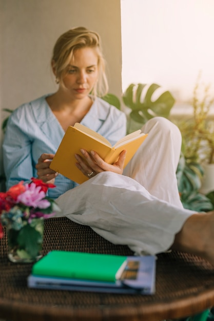 Blonde young woman reading book with vase on table Free Photo