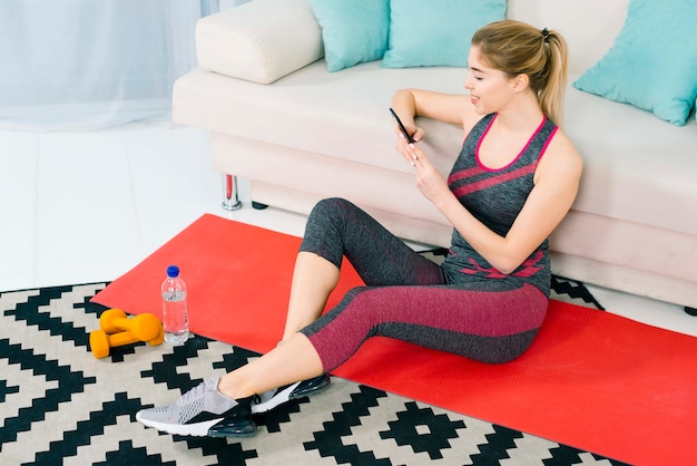 Blonde young woman sitting on carpet at home using mobile phone Free Photo