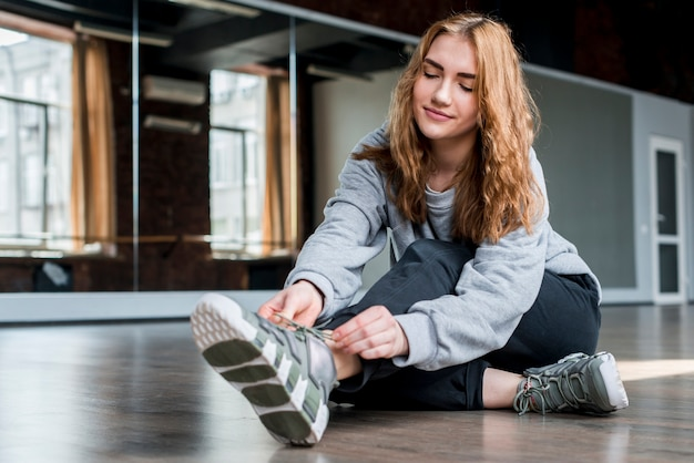 Blonde young woman sitting on floor tying shoelace Free Photo