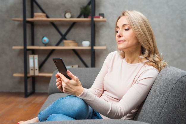 Blonde young woman sitting on sofa using smart phone at home Free Photo