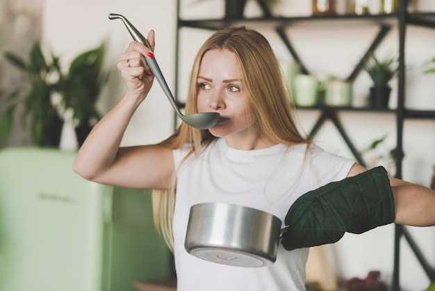 Blonde young woman tasting soup from the ladle Free Photo