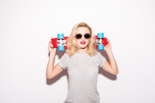 Blondie con skateboard rosso rimane davanti al muro bianco Foto Gratuite