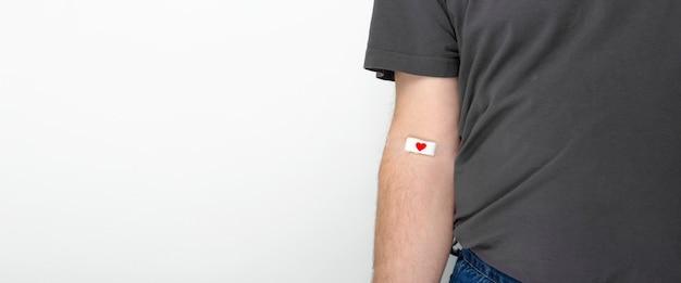 献血。灰色の背景に血を与えた後、赤いハートのパッチでテープで留められた灰色のtシャツの手の男。 Premium写真