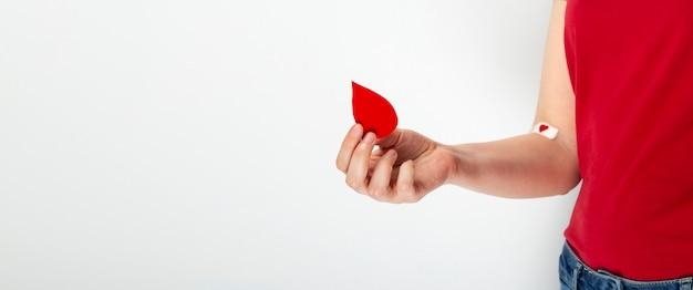 献血。赤いtシャツの少女は、灰色の背景に血を与えた後、赤いハートのパッチがテープで貼られた秒針を手に落とします。 Premium写真