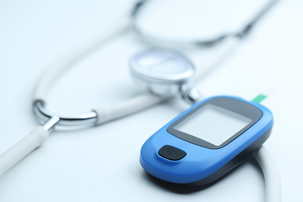 Blood glucose meter and stethoscope on white background Free Photo