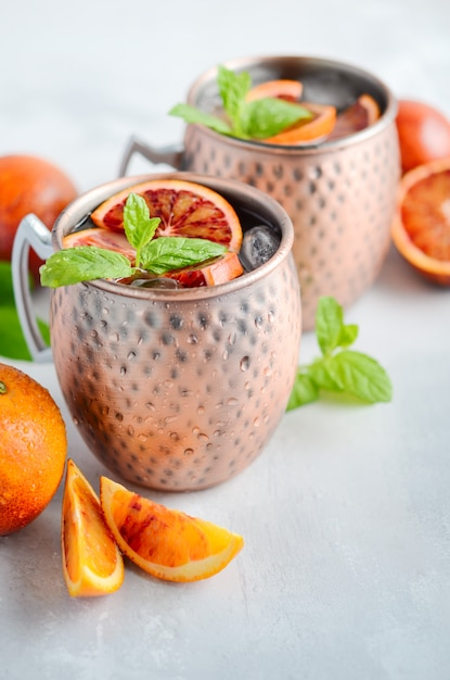Blood orange moscow mule alcohol cocktail with fresh mint leaves and ice in copper mugs on a gray concrete background. Premium Photo