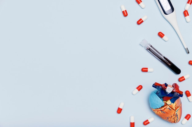 Blood sample and heart figurine copy space Free Photo