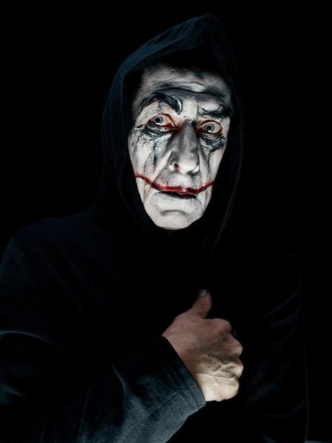 Tema di halloween sanguinante: il folle volto di maniak in studio scuro Foto Gratuite