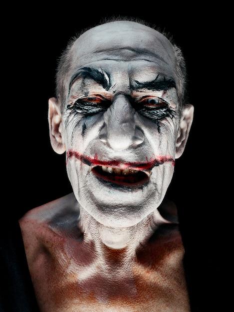Tema di halloween sanguinante: il folle volto di maniak sorridente in studio scuro Foto Gratuite