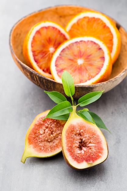 灰色のテーブルに血まみれのシチリアオレンジとイチジク Premium写真
