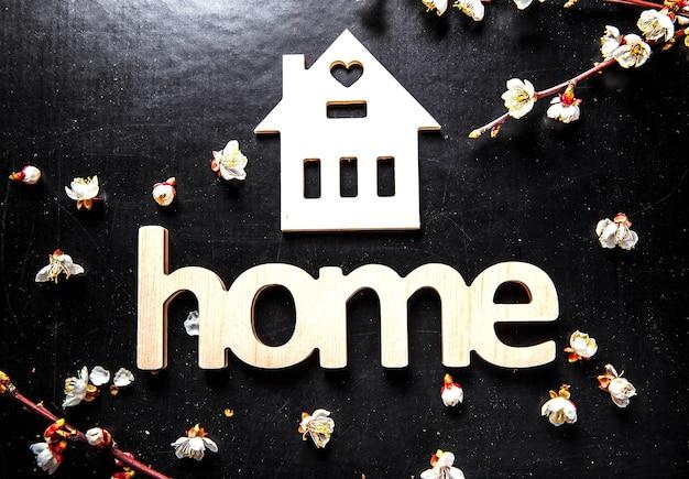 黒い背景と家という言葉で木製の看板に咲く Premium写真