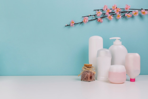 Blooming twig over cosmetics bottles and jar Free Photo