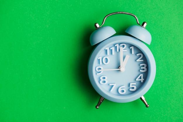 Blue alarm clock against green background Premium Photo