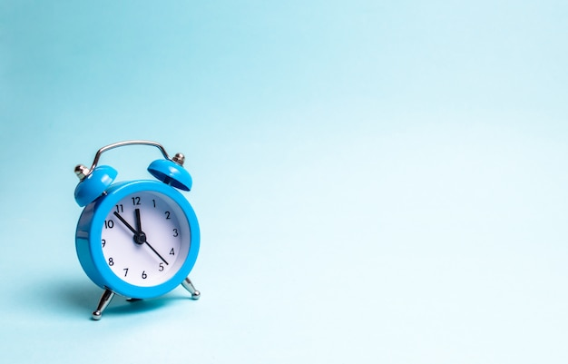 A blue alarm clock on a light blue background. the concept of waiting for a meeting, a date. Premium Photo