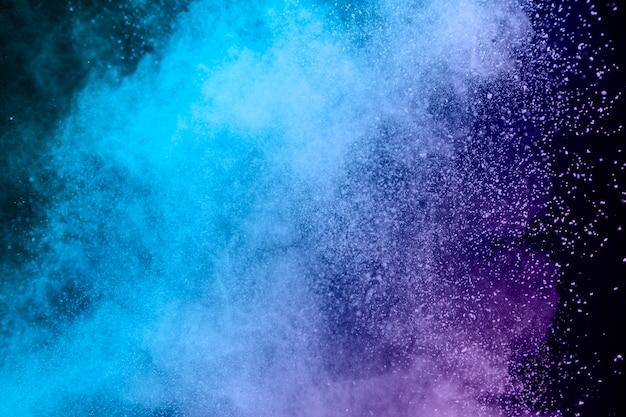 暗い背景上の粉の青と紫のほこり Premium写真