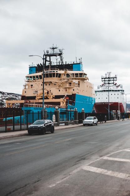 Синий и белый корабль на пристани в дневное время Бесплатные Фотографии