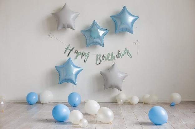 파란색과 흰색 별 풍선과 흰 벽에 비문 생일 축하 해요. 생일 장식 프리미엄 사진