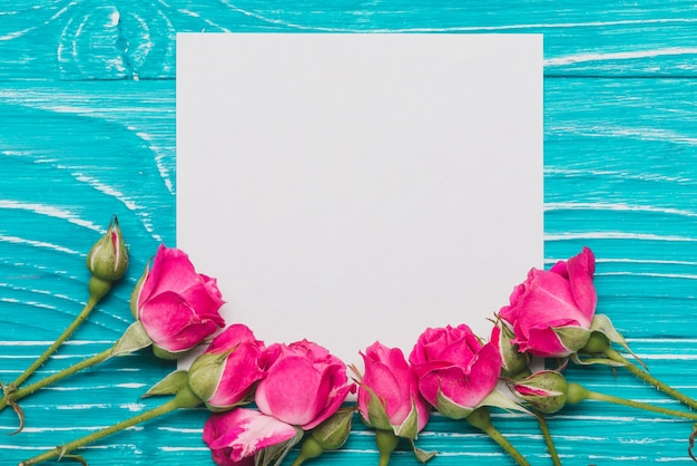 Blue background with paper and roses Free Photo