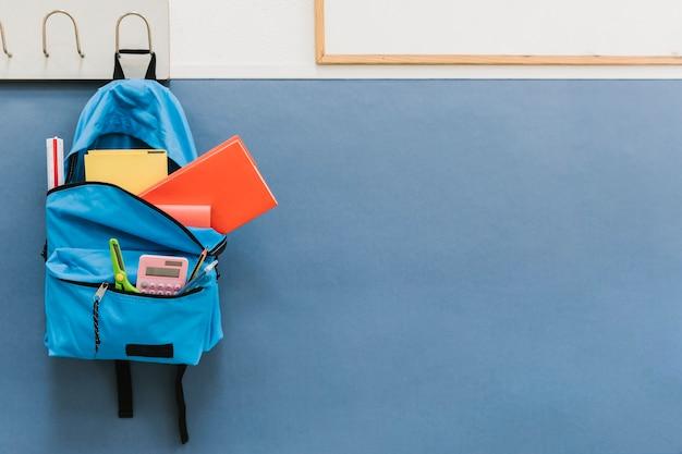 Blue backpack on hook in school Premium Photo