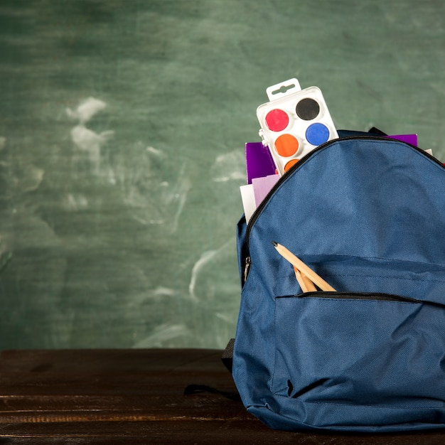 Blue backpack with stationery and watercolors Free Photo