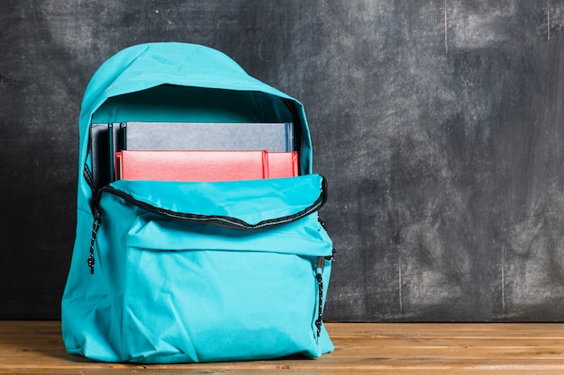 Blue backpack with textbooks Free Photo