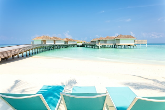 Blue beach chairs on white sand with wooden jetty and tropical villas in maldives on background, tropical holiday. Premium Photo