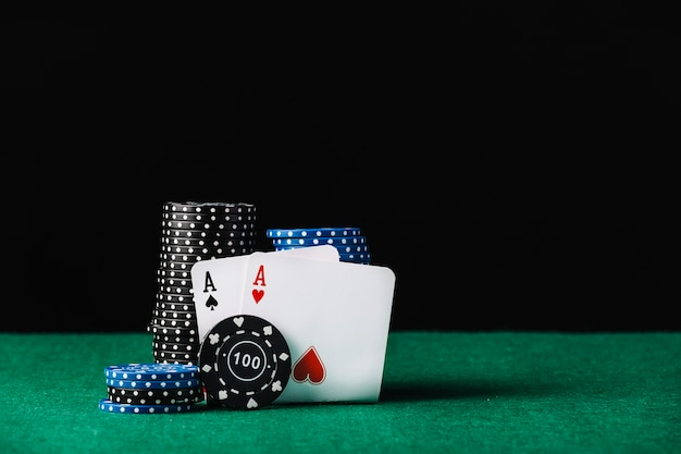 Blue and black casino chips stack with heart and spade aces Premium Photo