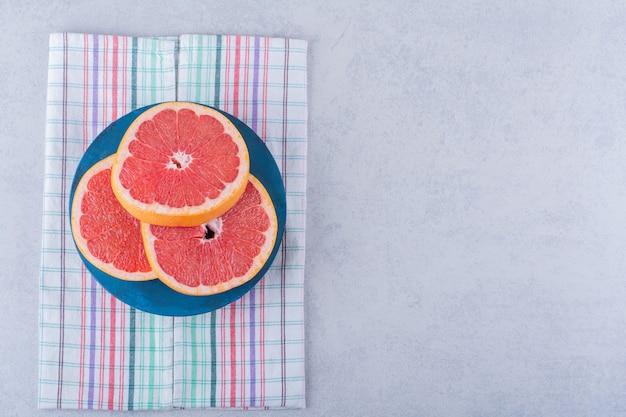 石のテーブルに新鮮なグレープフルーツのスライスの青いボード。 無料写真