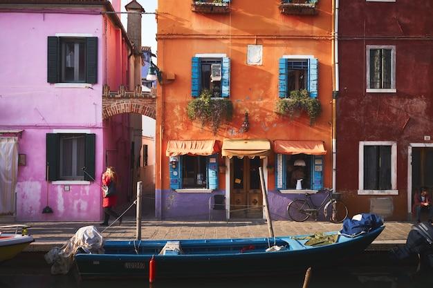 オレンジ色の建物の近くの川の青いボート 無料写真