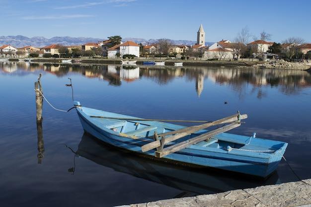 村のドックに沿って結ばれた青いボート 無料写真