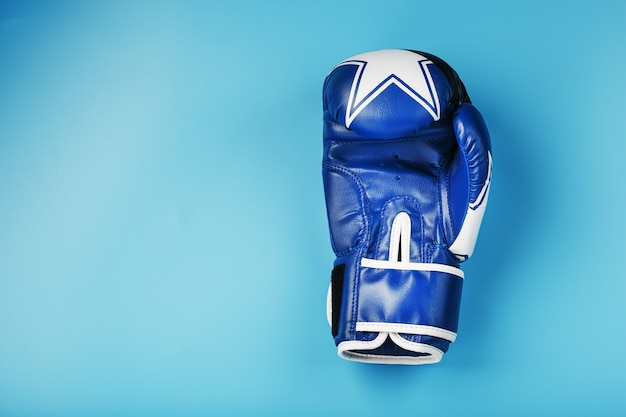 Blue boxing glove on a blue background, free space Premium Photo