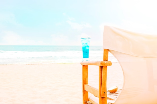Blue bright drink on arm of wooden chair and coconut Free Photo