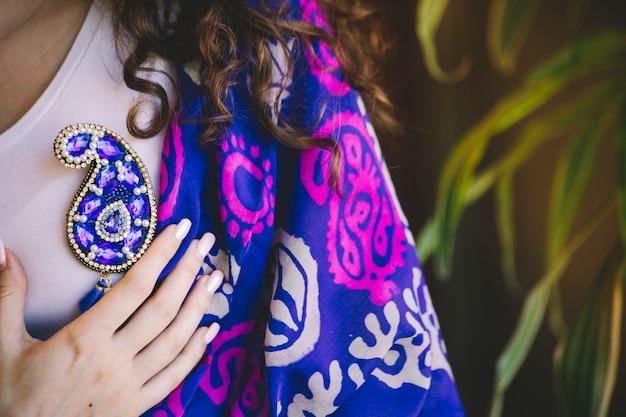 青いブタの形のジュエリーピンとシルクのショール 無料写真