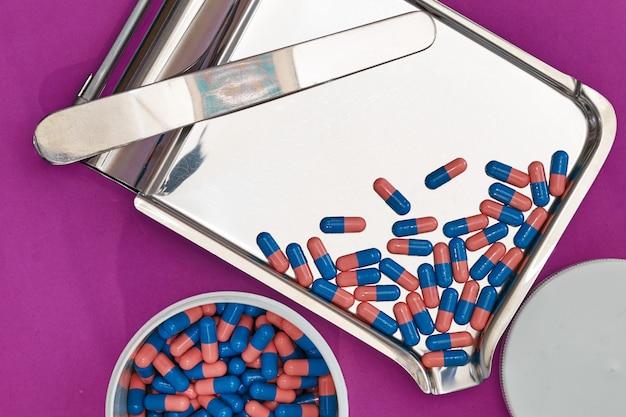 보라색 배경에 약국 가게에서 항아리와 트레이에 파란색 캡슐 프리미엄 사진