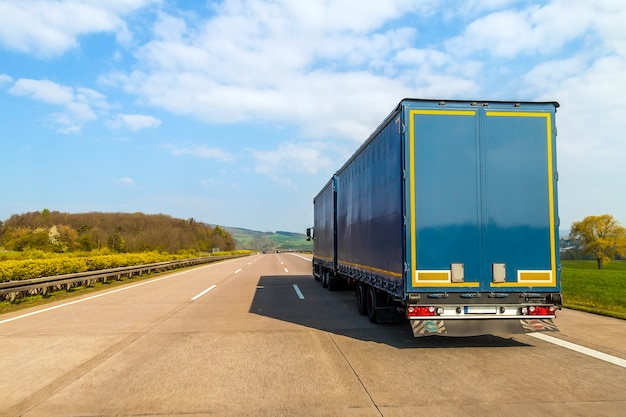 空の高速道路上の青い貨物トラック Premium写真