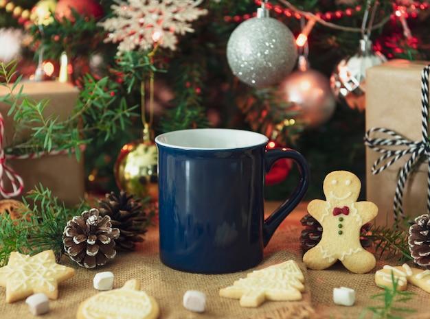 青いセラミックコーヒーカップとクリスマステーブルデコレーション。創造的な広告テキストメッセージまたはプロモーションコンテンツのモックアップ。 Premium写真