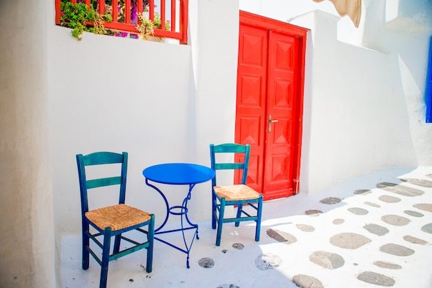Blue chairs and table on street of typical greek traditional village with white houses on mykonos island, greece, europe Premium Photo