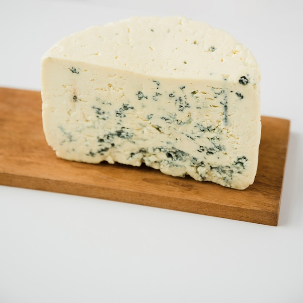 Blue cheese chunk on wooden board against white background Free Photo