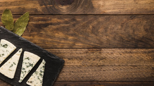 Blue cheese slice arrange on black slate with bay leaves over old wooden desk Free Photo