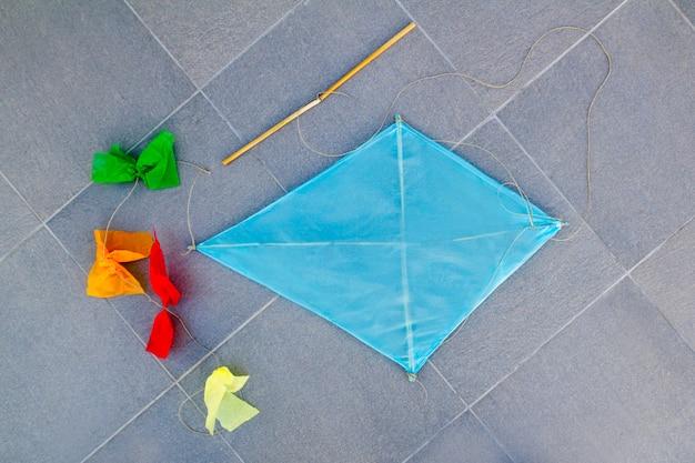 Blue children kite traditional diamond shape on floor Premium Photo