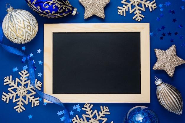 青いクリスマス背景、モックアップ。 ch板の周りの冬の銀の装飾の平面図。コピースペース。 Premium写真
