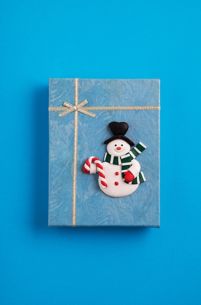 Blue christmas gift box decorated with a snowman in the blue background Free Photo