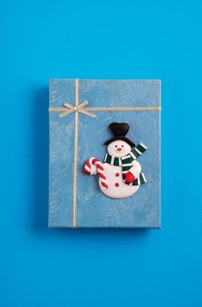 Confezione regalo di natale blu decorata con un pupazzo di neve sullo sfondo blu Foto Gratuite