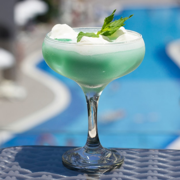 Blue cocktail in a beautiful glass with ice cream and green mint leaves Premium Photo