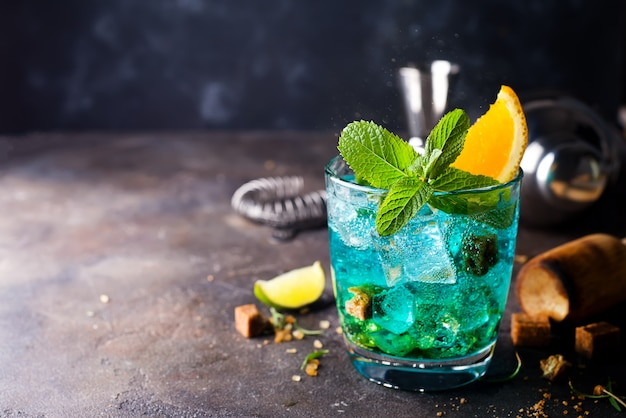 Blue cocktail in glasses with ice, mint and orange Premium Photo
