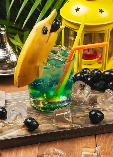 Blue cocktail with banana dolphin decoration, black grapes on a wooden board Free Photo